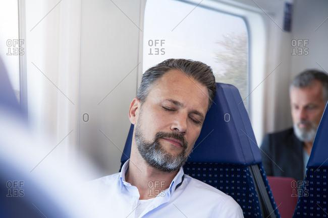 Mature man sitting in a train- sleeping