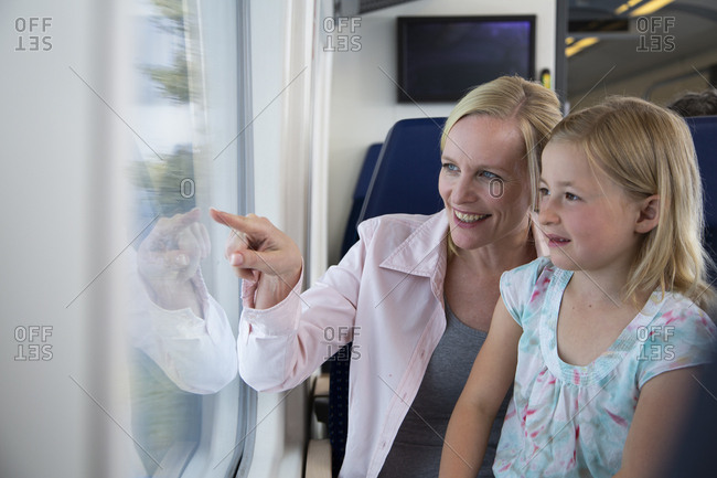 Mother and daughter traveling by train- pointing out of window