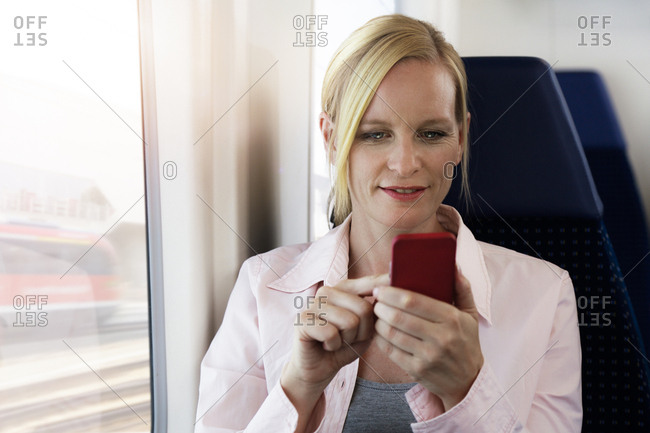 Woman using smartphone on a train