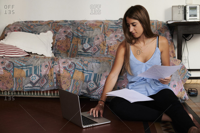 Female student studying at home- using laptop