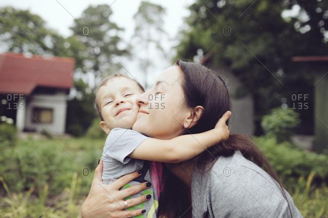 Affectionate mother hugging toddler in garden