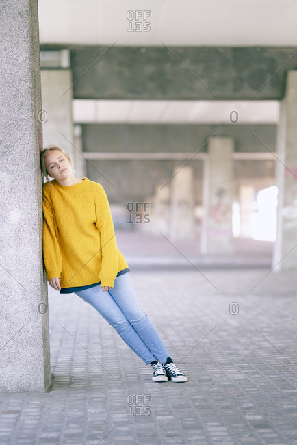 Portrait of young woman with eyes closed leaning against pillar