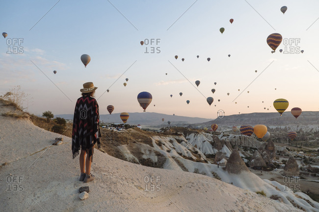 Young woman and hot air balloons in the evening- Goreme- Cappadocia- Turkey