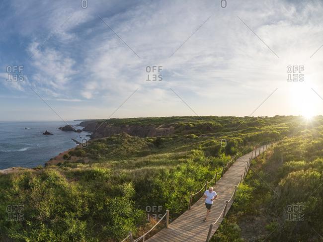 Portugal- Alentejo- senior man jogging on wooden boardwalk