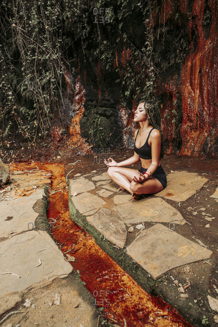 Young woman meditating at a waterfall