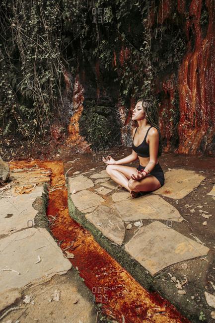 Young woman meditating at a waterfall