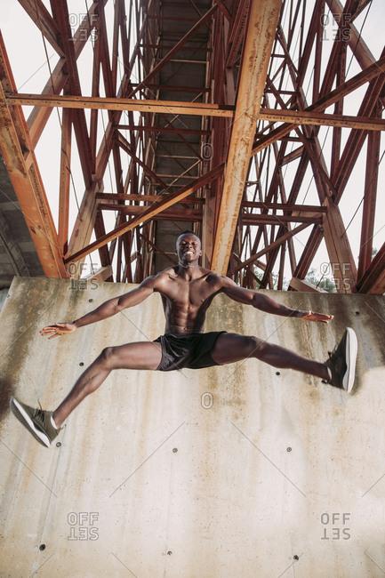 Young man jogging under a bridge