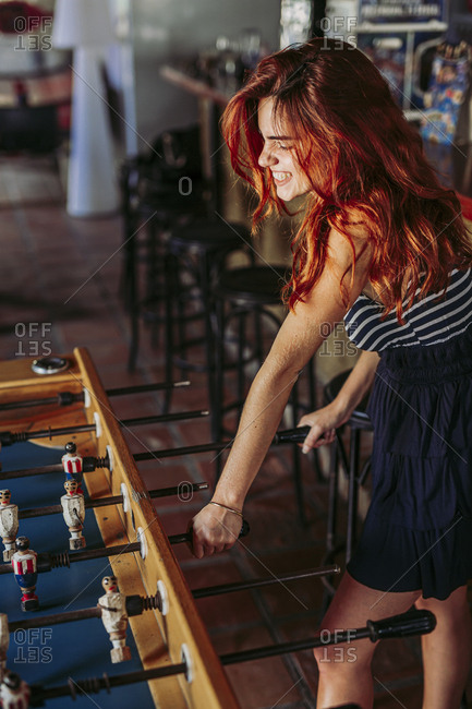 Young woman playing foosball in a sports bar
