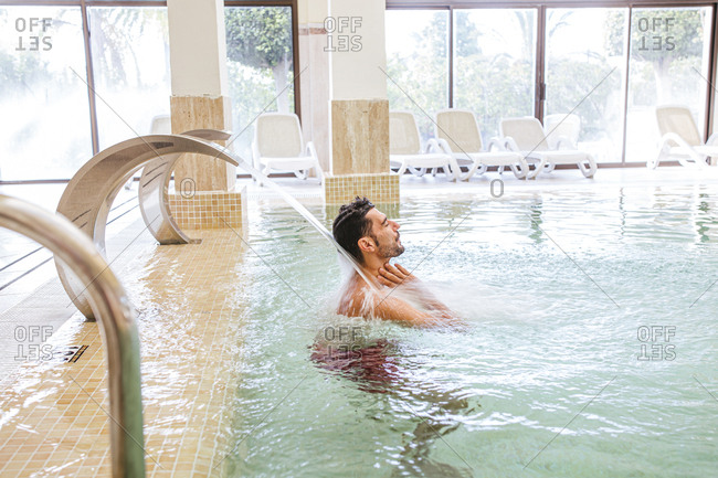 Man relaxing in swimming pool of a spa