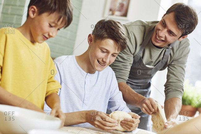 Brothers preparing pizza dough in kitchen