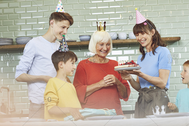Mother and sons celebrating grandmother's birthday in their kitchen