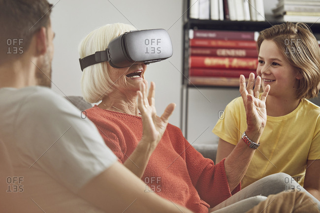 Grandmother using VR glasses with her grandsons