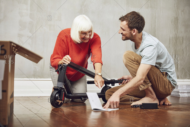 Grandson explaining e-scooter to his grandmother