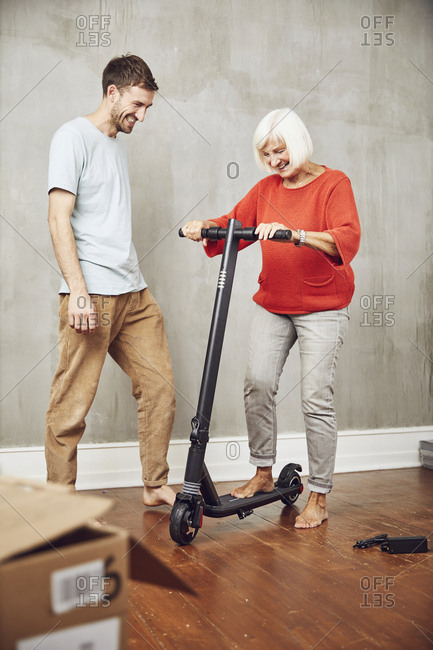 Senior woman trying out her new e-scooter- grandson assisting