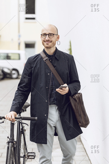 Man with bicycle going to work holding his smartphone