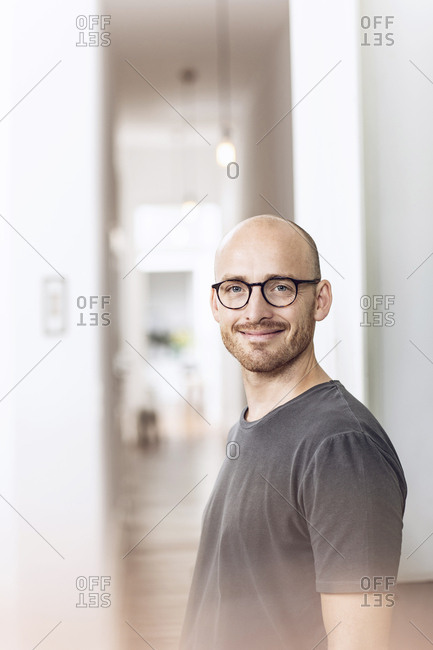 Smiling man standing in the morning at home in the kitchen
