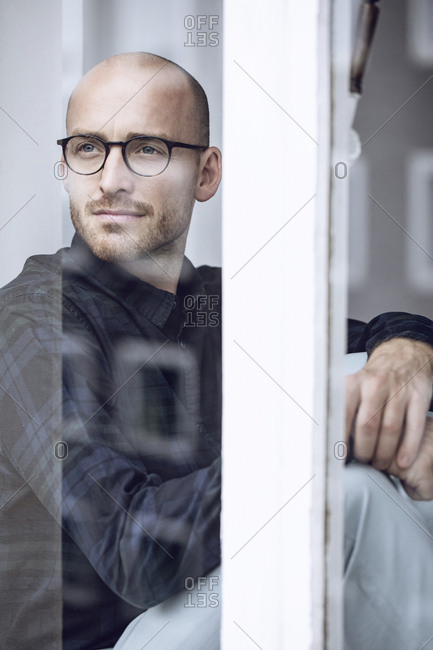 Man looking thoughtfully out the window
