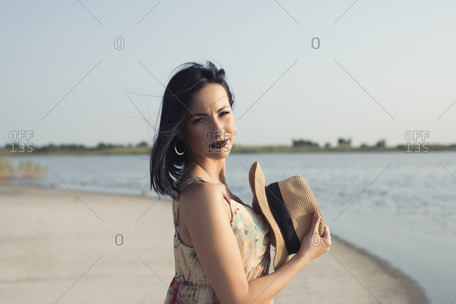 Portrait of a beautiful woman holding a hat at a lake