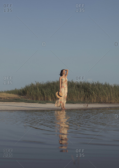Beautiful woman in a summer dress standing at a lake