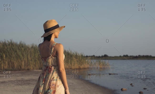 Woman in a summer dress standing at a lake