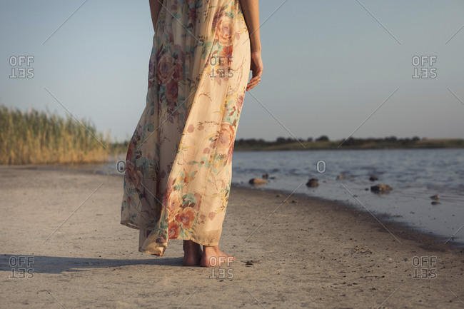 Low section of woman in a summer dress standing at a lake