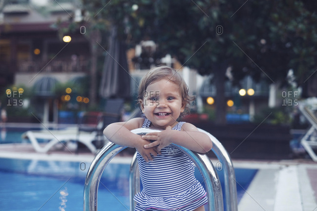 Portrait of cute little girl by the poolside