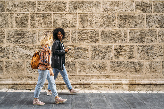 Multicultural happy women walking in the city- using smartphone