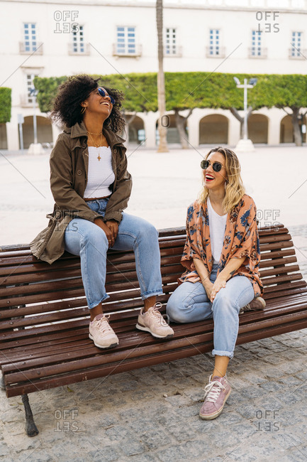 Multicultural happy women sitting on bench