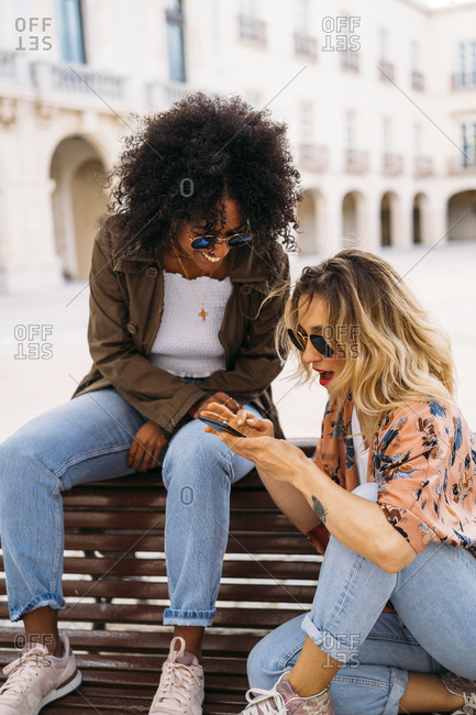 Multicultural happy women talking and using smartphone- sitting on bench