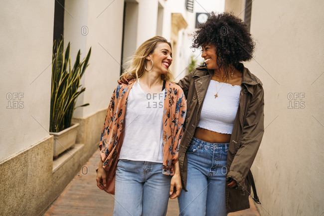 Multicultural laughing women walking in the city
