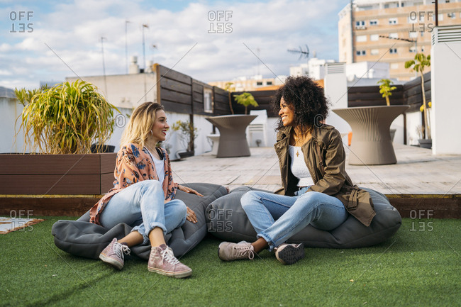Multicultural women talking sitting on cushions on a terrace