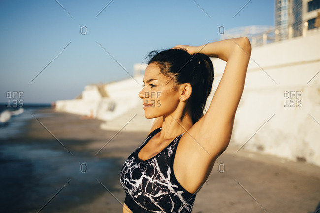 Woman during workout- stretching arm on the beach