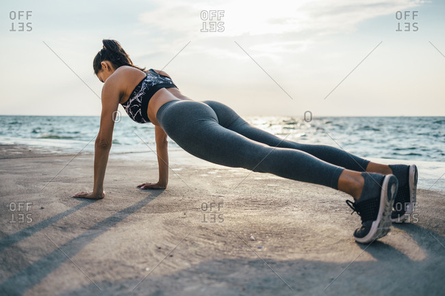 Woman during workout on a pier- push up