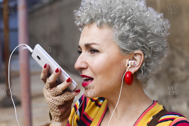 Portrait of pierced mature woman with grey curly hair using earphones and cell phone