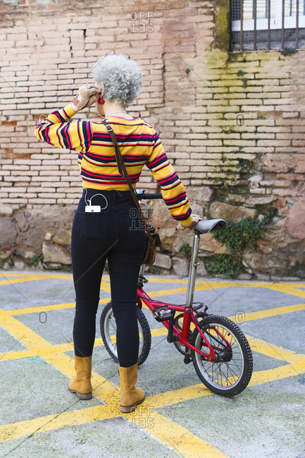 Back view of woman with bicycle carrying smartphone in her pocket
