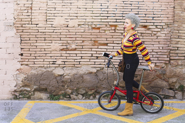 Fashionable mature woman with bicycle and smartphone on the street