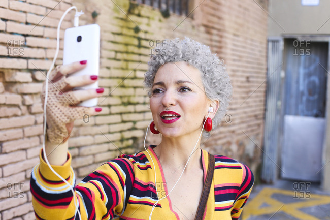 Portrait of mature woman with red lips and grey hair taking selfie with cell phone