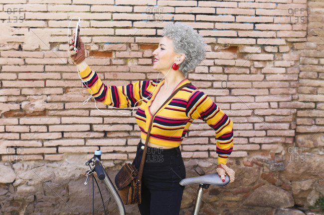 Smiling mature woman with bicycle taking selfie with cell phone
