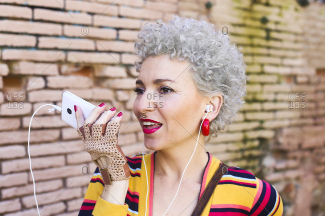 Portrait of pierced mature woman with ear phones on the phone
