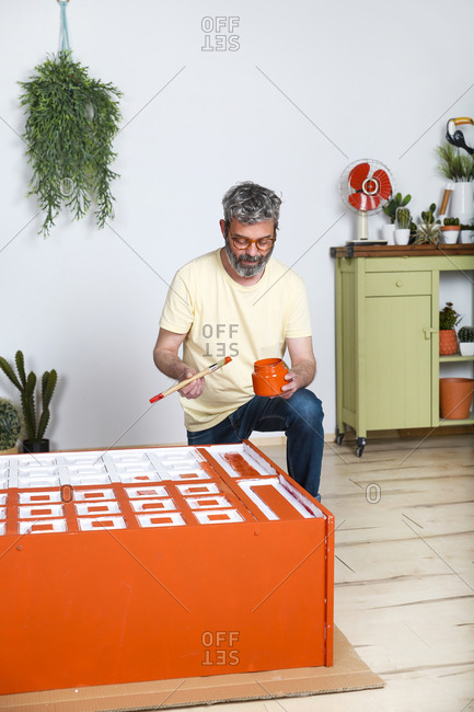 Man painting furniture with brush at home