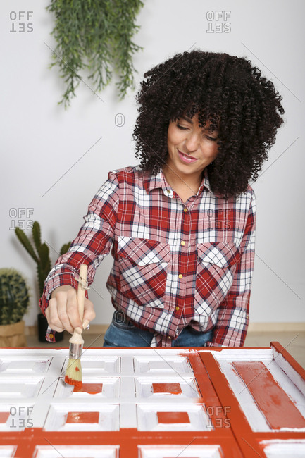 Woman painting furniture with brush at home