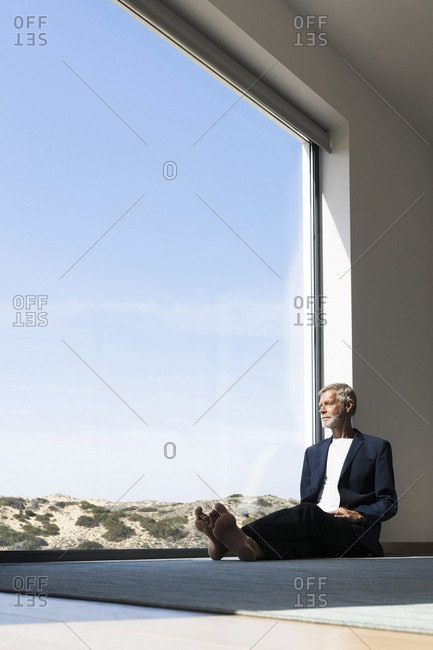 Senior businessman sitting at panorama window looking out