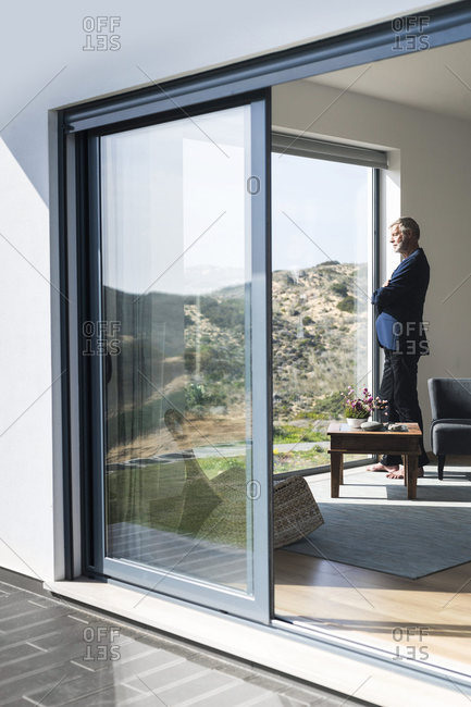 Senior businessman standing at panorama window looking out