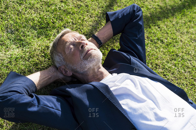 Senior businessman lying in grass with closed eyes
