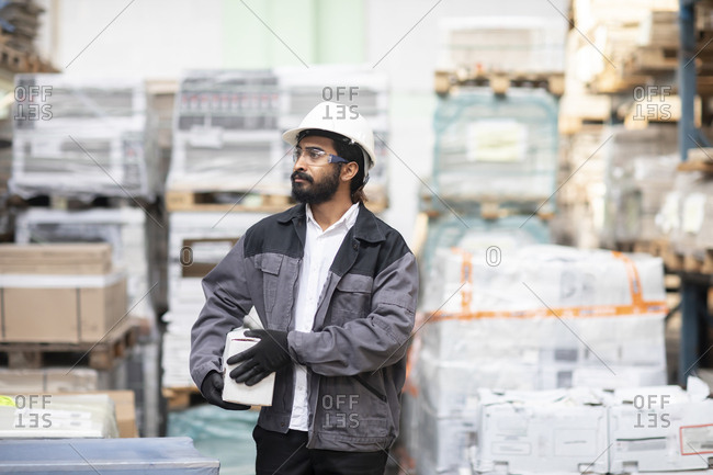 Young man wearing hard hat working in a warehouse carrying a box
