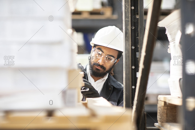 Young man wearing hard hat working in a warehouse