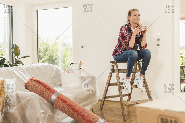 Woman moving into new home having a coffee break