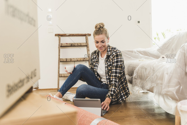 Woman sitting on the floor in new home using tablet