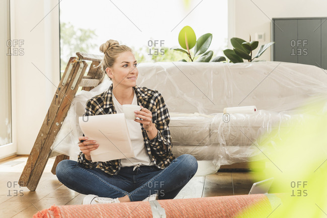 Woman sitting on the floor in new home with a plan