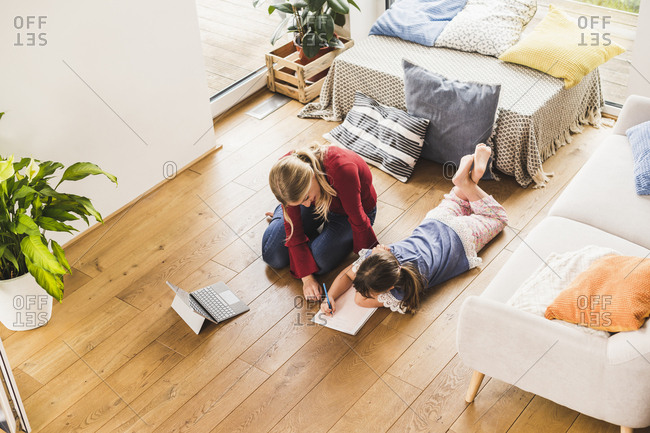 Mother helping daughter with homework at home
